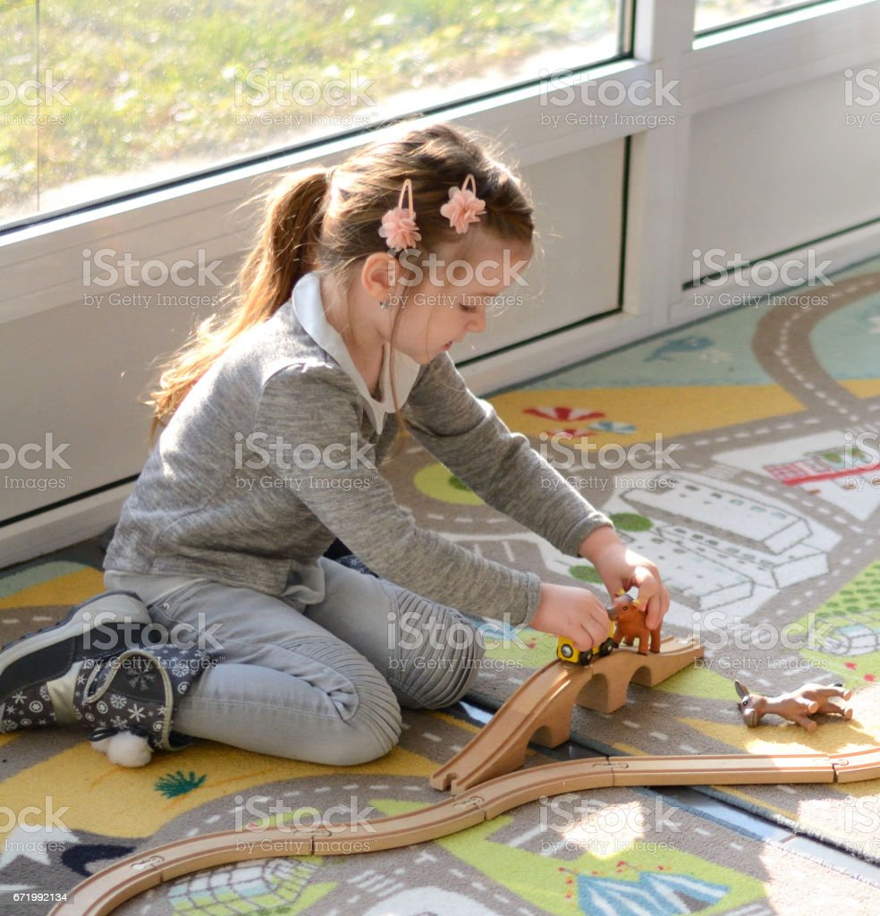 Little girl plays with toys, wooden train, railway and animals stock photo