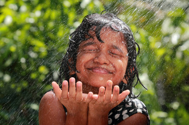 kleines mädchen spielt mit wasser - regenzeit stock-fotos und bilder
