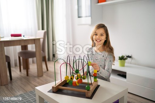 Beautiful little girl is playing with wooden maze toy