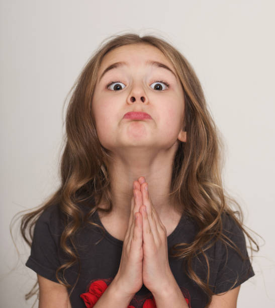 Little girl pleading with hands clasped together Oh please, may I please. Cute little girl pleading with hands clasped together, with funny grimace pleading stock pictures, royalty-free photos & images