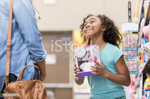 Elementary age girl pleads with her mom to buy her a toy while shopping.