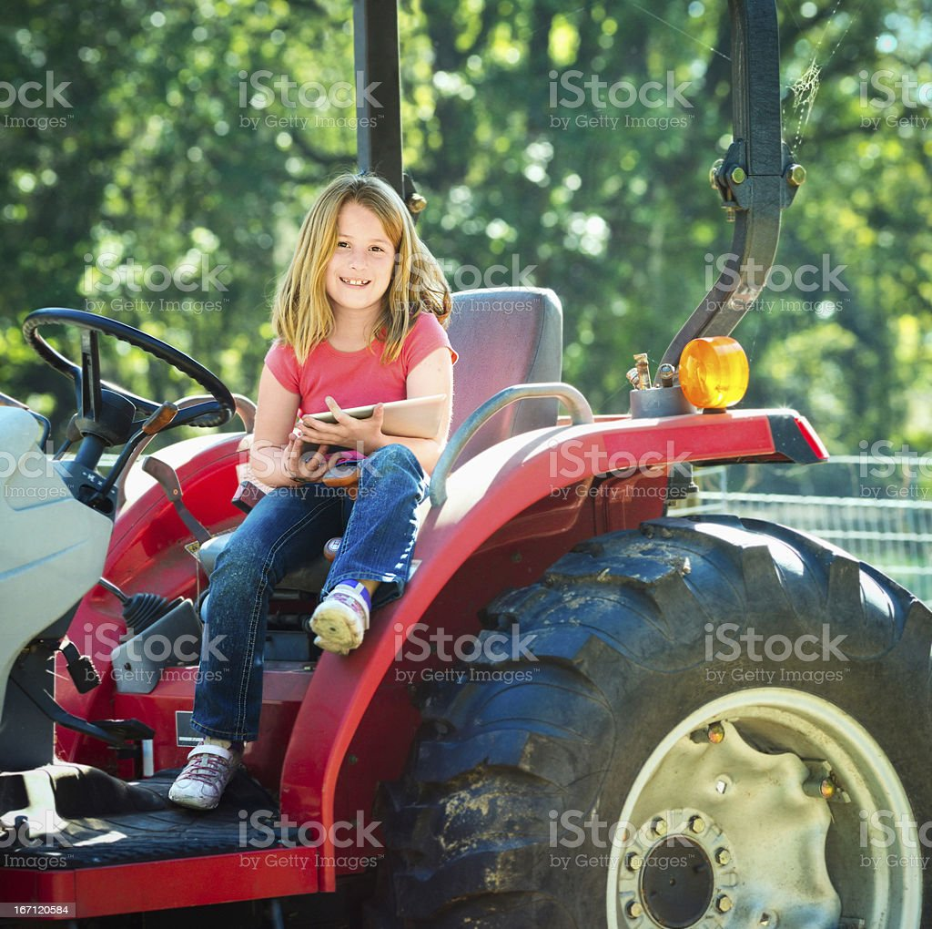 Little Girl portrait on tractor with Digital Tablet royalty-free stock photo
