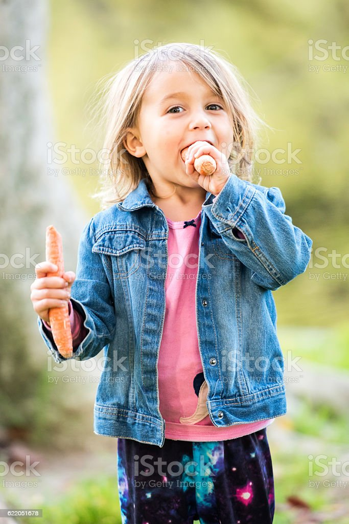 Little Girl Posing At A Park Eating Carrots