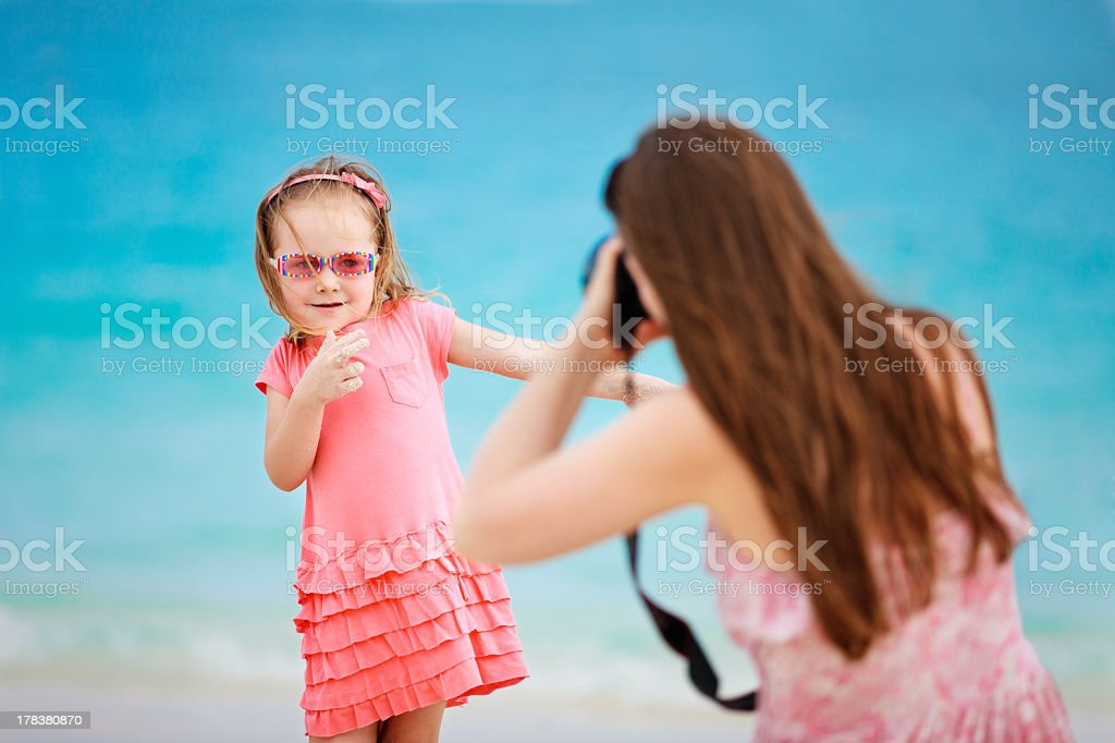 A little girl posing for her mom for a picture at the beach royalty-free stock photo