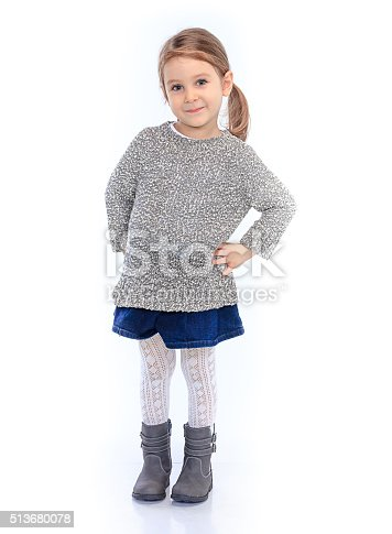 A cute young girl posing smiling standing over a white background