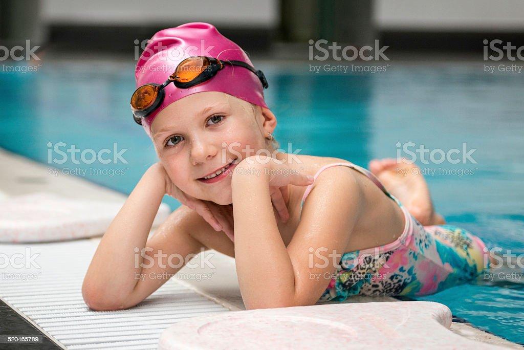 Little girl posing on the swimming pool edge stock photo