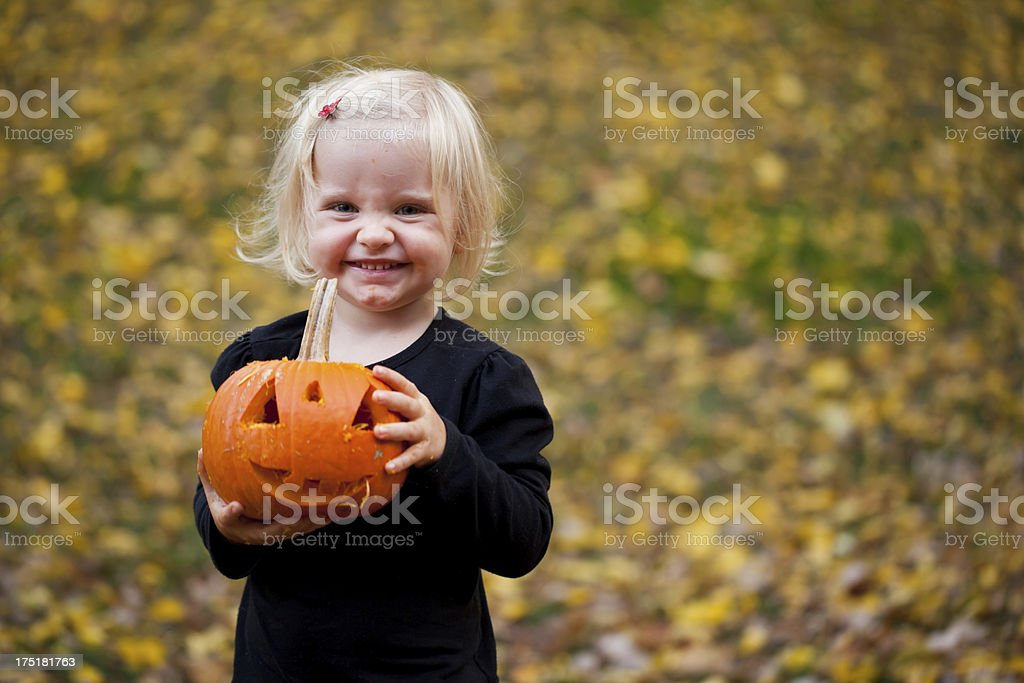Little girl posing with Halloween pumpkin royalty-free stock photo