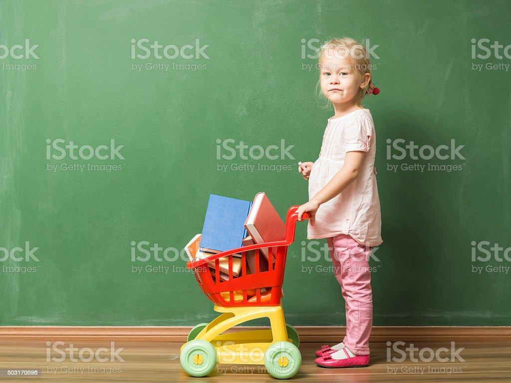 Little Girl Posing With Shopping Cart Full Of Books stock photo