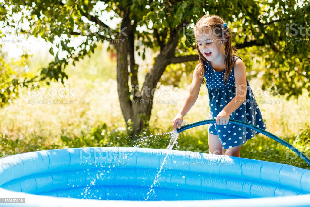 Little girl pouring water into a small pool stock photo