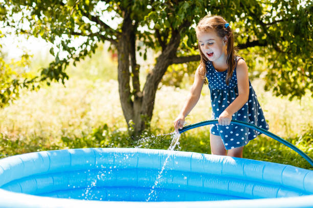 little girl pouring water into a small pool - competition group stock photos and pictures