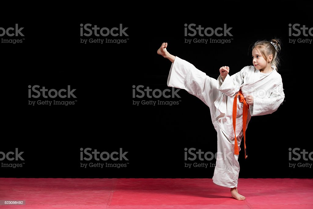 Little girl practice karate isolated on black stock photo
