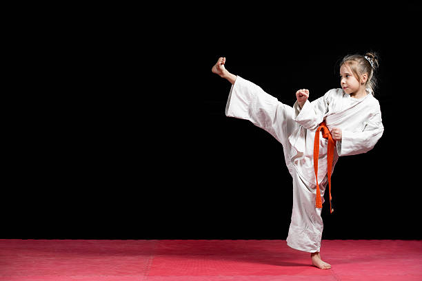 little girl practice karate isolated on black - karate stock photos and pictures