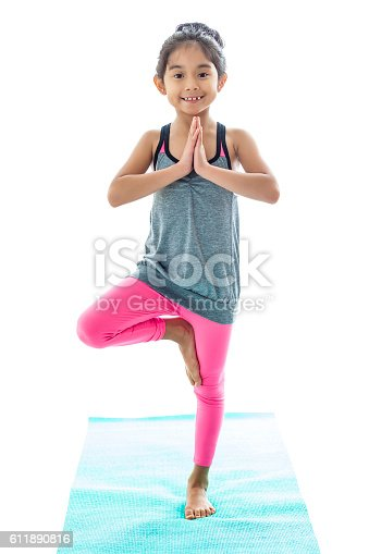 istock Little girl practices tree pose in yoga class 611890816
