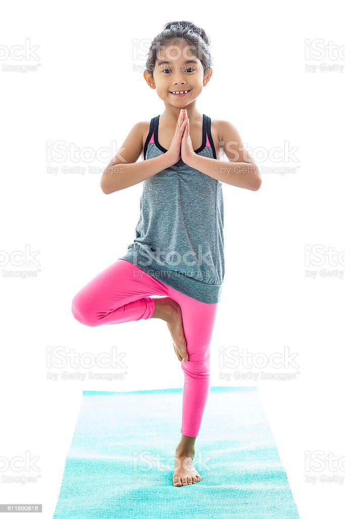 Little girl practices tree pose in yoga class stock photo