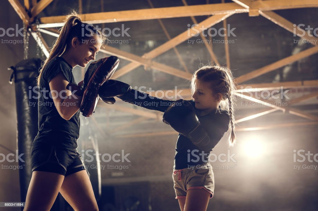 Little girl practicing boxing with her coach in health club. stock photo