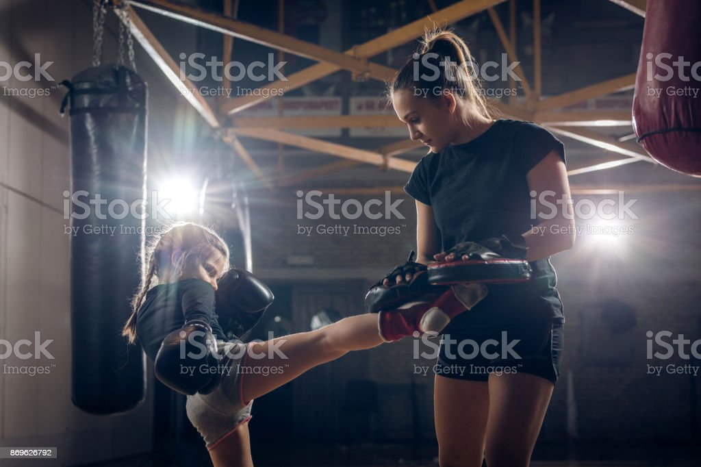 Little girl practicing kickboxing with her coach in health club. stock photo