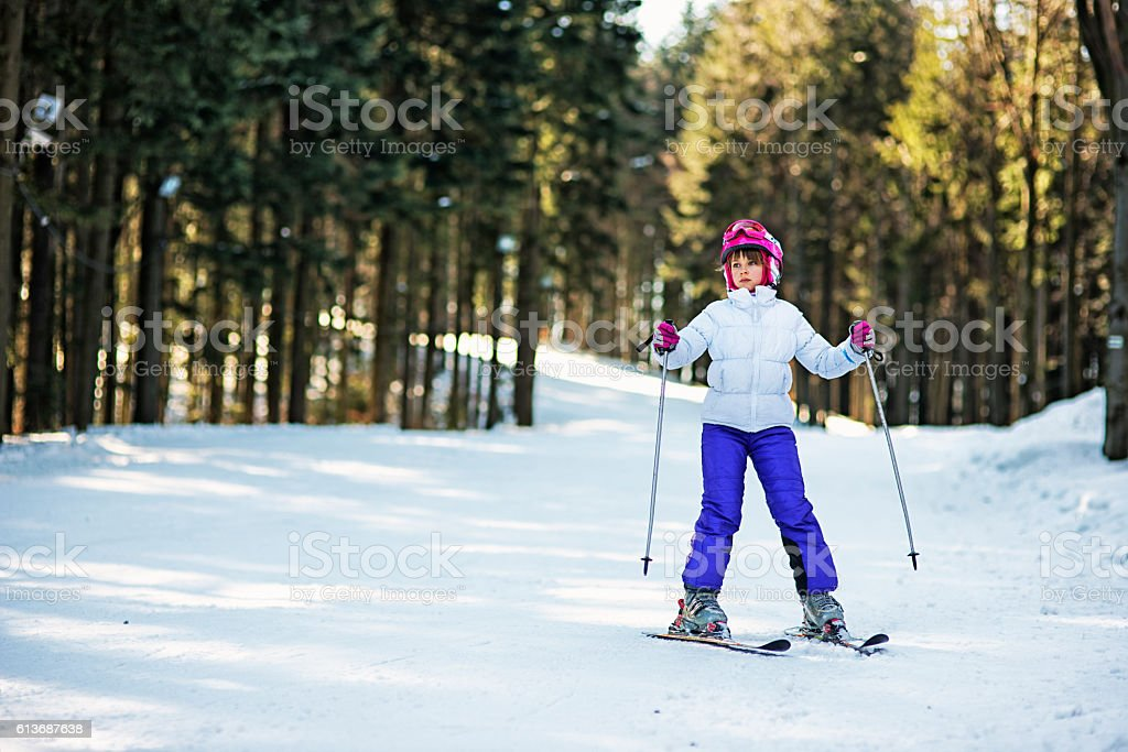 Little girl practicing skiing on ski lesson stock photo