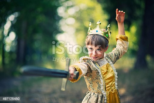 Little 9 year old princess practicing sword play in forest. The girl is wearing princess dress and crown and is wielding a sword with obvious proficiency.