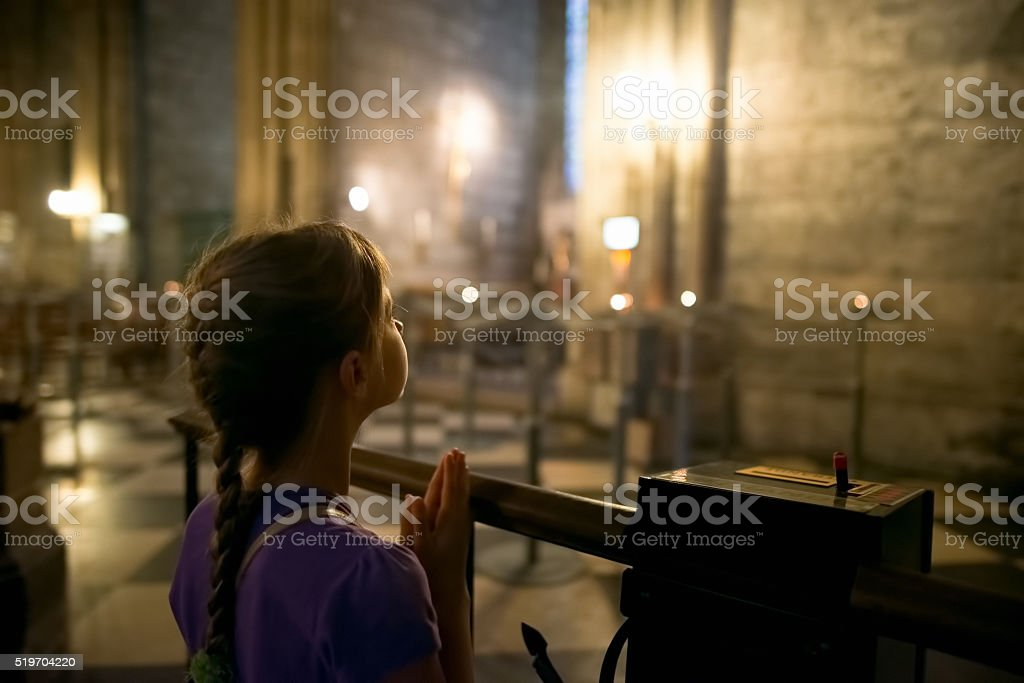 Little girl praying at the church stock photo