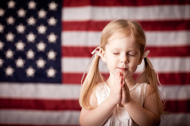 Little Girl Praying in Front of American Flag stock photo
