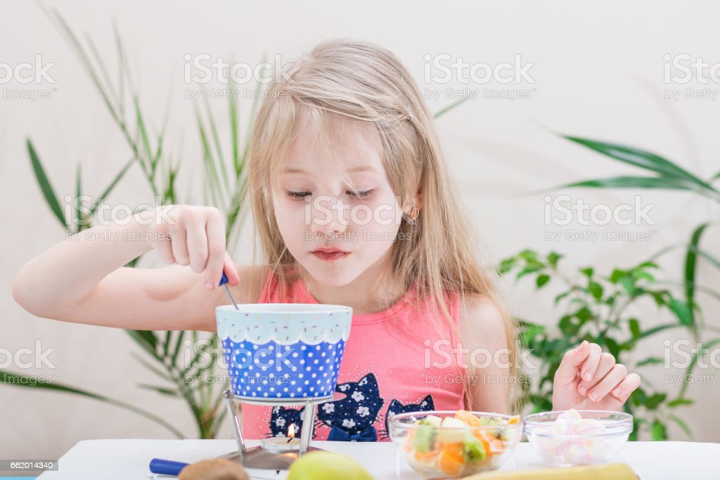 Little girl preparing and eating a chocolate fondue. royalty-free stock photo