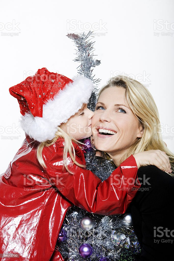 little girl preparing christmas tree kissing her mother royalty-free stock photo