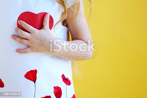little girl presses a red paper heart to her chest. Health and Valentine's day concept
