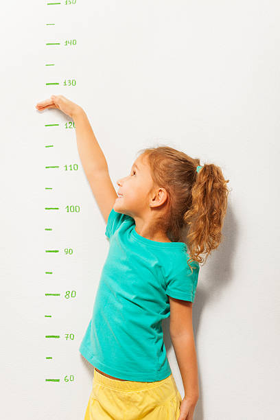 little girl pretend how high she is on wall scale - height measurement stock photos and pictures