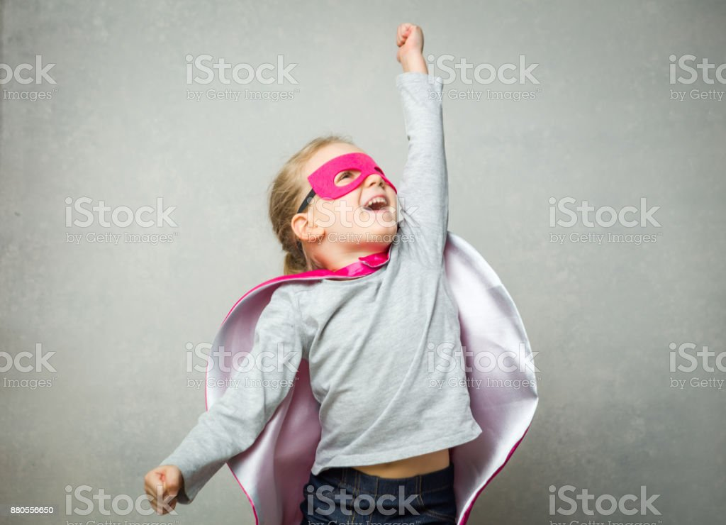 Little girl pretending that she is flying wearing a cloak and mask stock photo