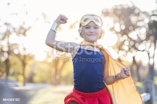 Little girl enjoys dressing up as a superhero. She is smiling at the camera while flexing her muscles.