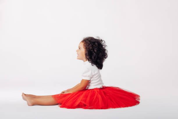 kleine mädchen prinzessin auf dem boden sitzend - festliche babymode junge stock-fotos und bilder