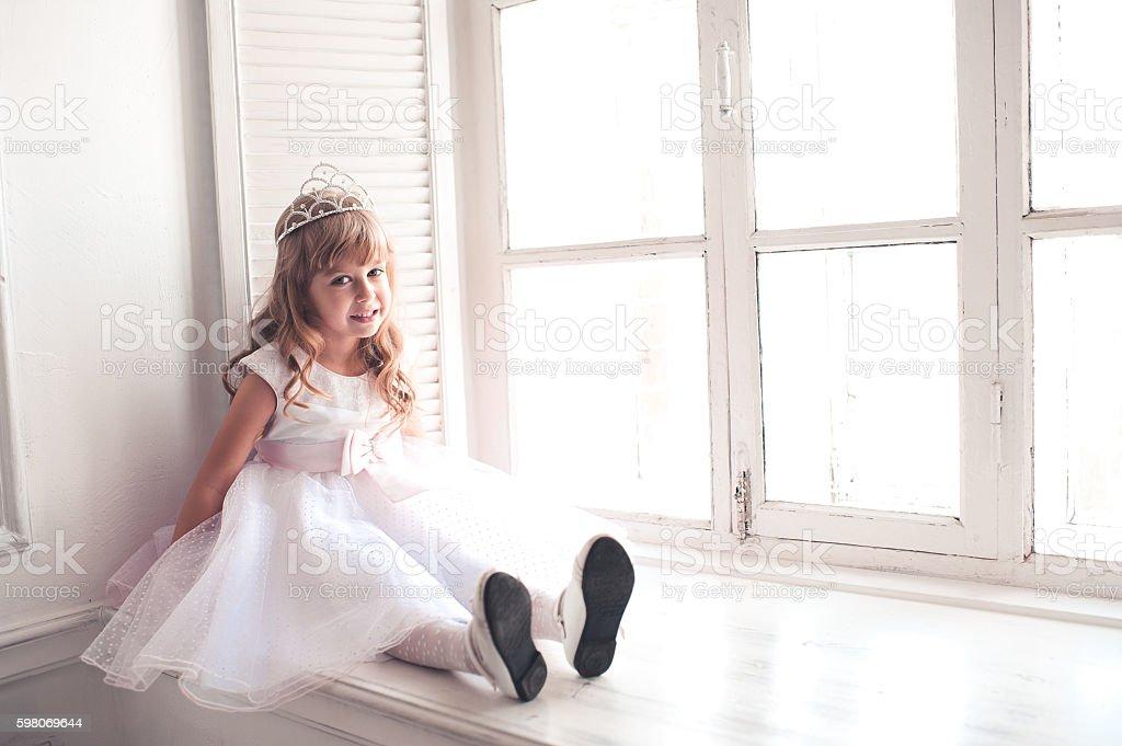 Little girl princess sitting on window sill stock photo