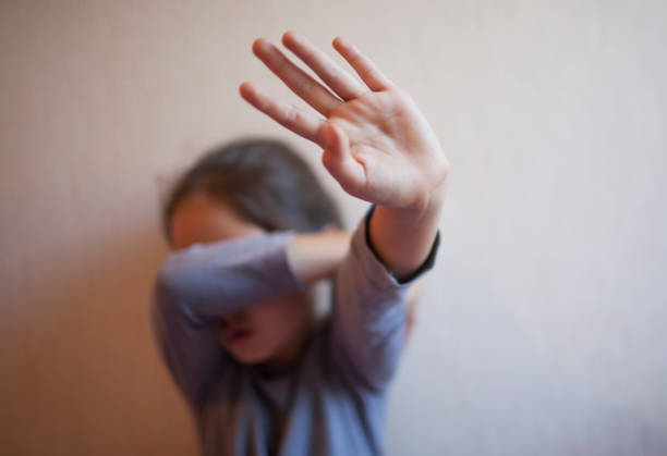 A little girl protects herself with her palm and covers her face A little girl protects herself with her palm trafficking stock pictures, royalty-free photos & images