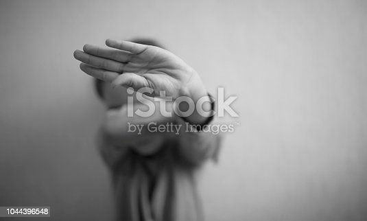 A little girl protects herself with her palm