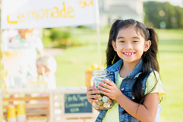 Little girl proudly sells lemonade in her front yard Cute Asian girl smiles while holding a jar full of cash and coins. She is set up a lemonade stand in the front of her home. The stand is in the background. lemonade stand stock pictures, royalty-free photos & images