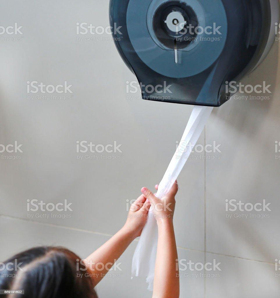 Menina puxando o papel higiênico fora do rolo. - foto de acervo