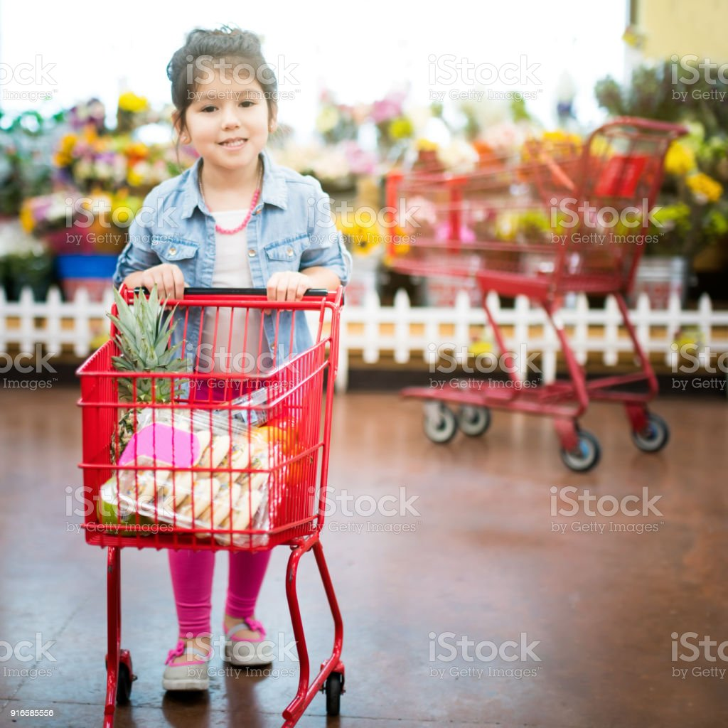 Little girl pushing a grocery cart stock photo