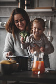 Little girl puts broccoli in the cooking pan while her mother holds her by the stove.