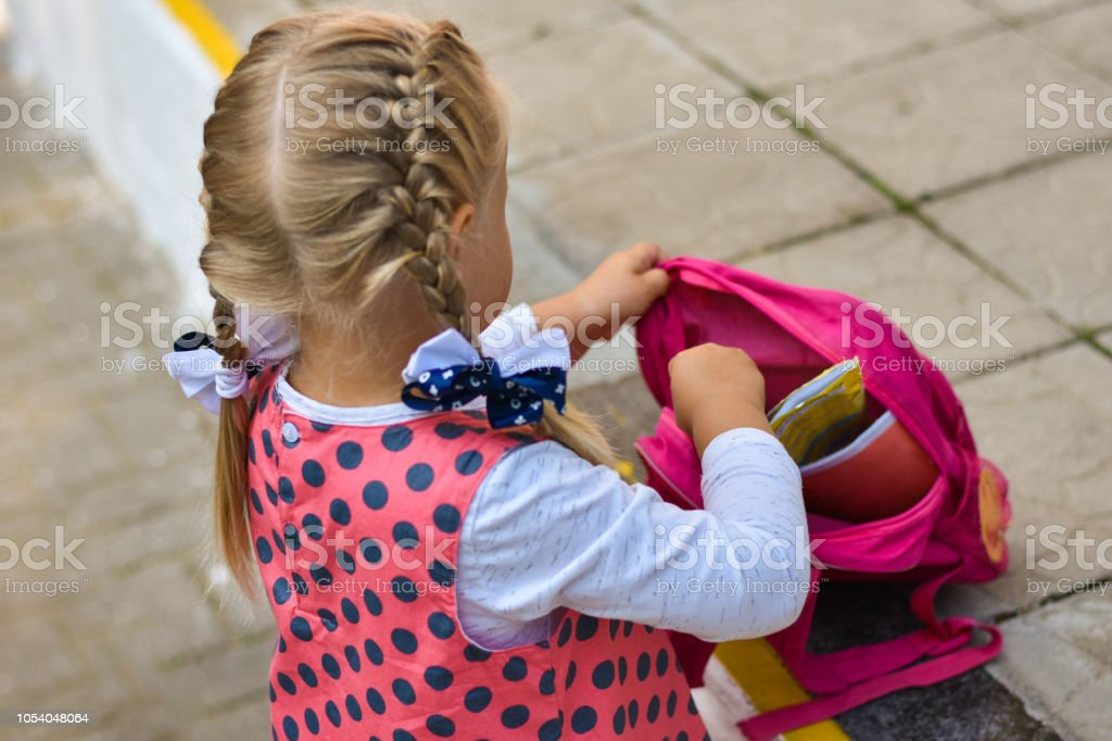 Little girl puts magazines, books and accessories in a backpack in a schoolyard stock photo