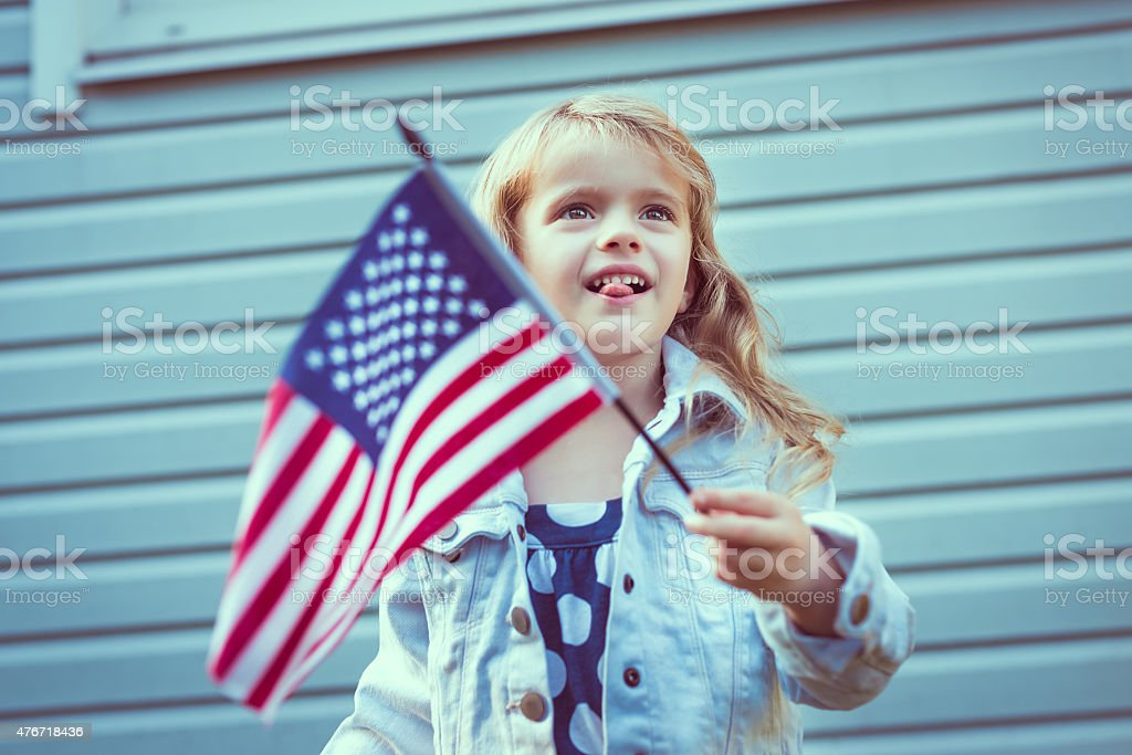 Little girl putting her tongue out and waving american flag stock photo