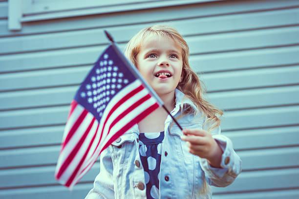 Kleines Mädchen putting Ihre Zunge heraus und winken Amerikanische Flagge – Foto