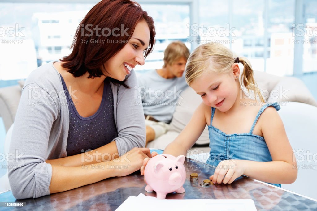 Little girl putting money in piggy bank with her parents stock photo