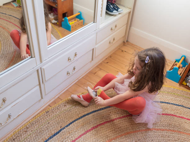 Little girl putting on ballet shoes in bedroom stock photo