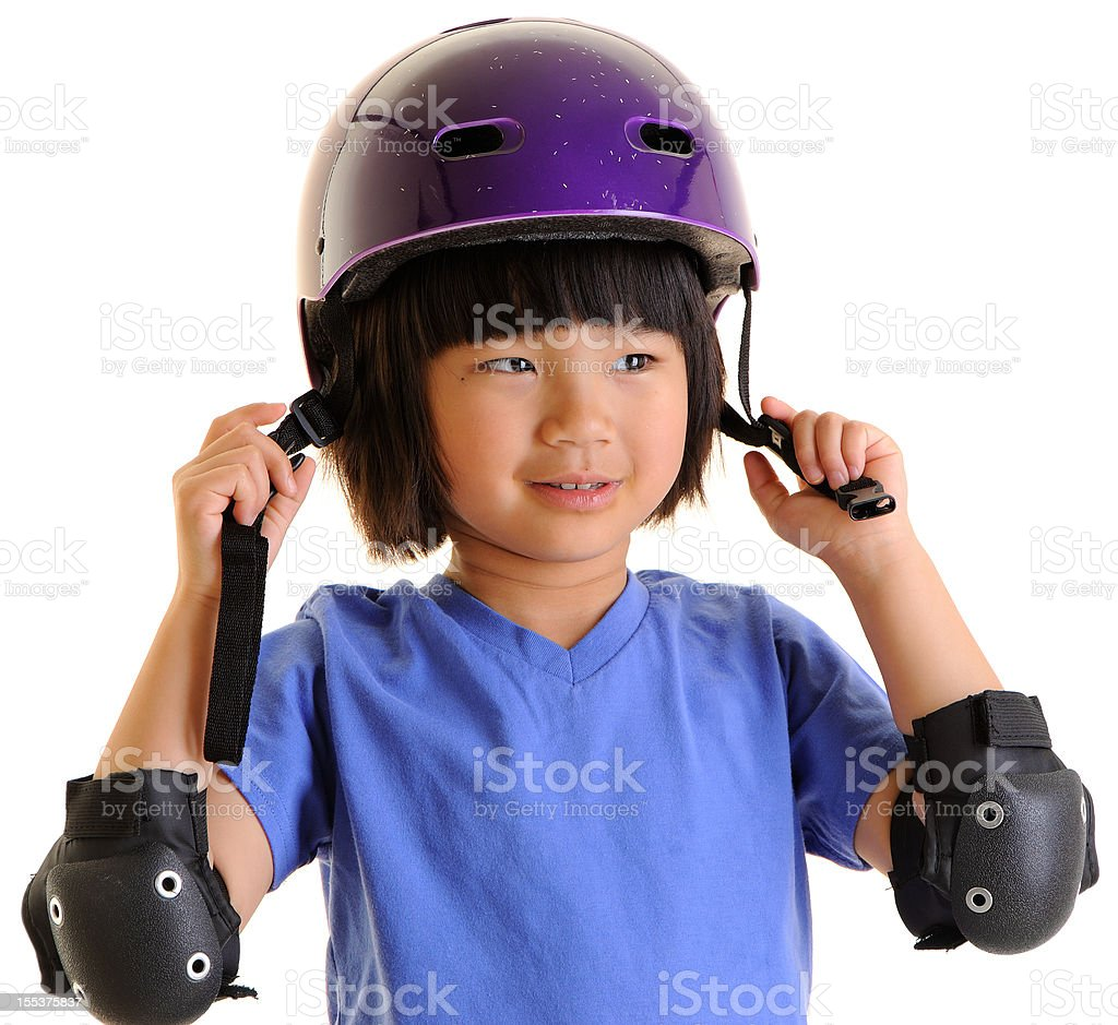 Little Girl Putting on Helmet and Elbow Pads stock photo