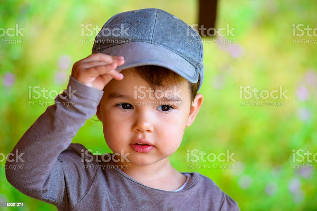 Little girl putting on her hat in summer time stock photo