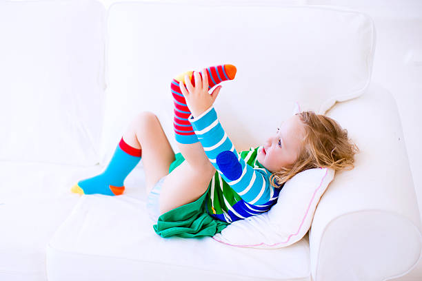 Little girl putting on socks stock photo