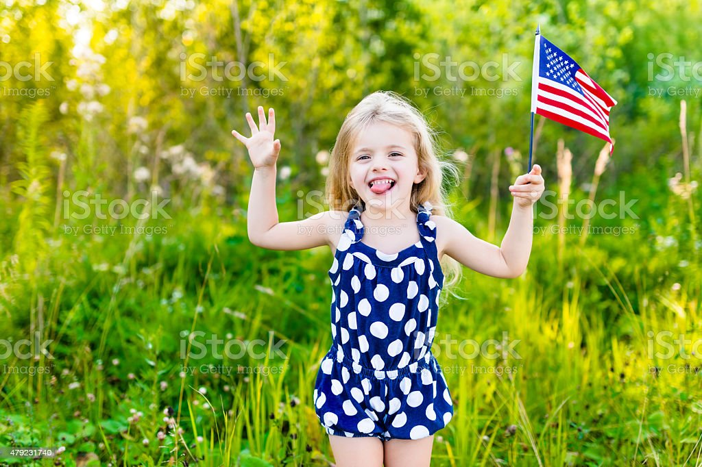 Little girl putting out her tongue and waving american flag stock photo
