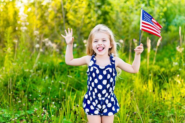 Kleines Mädchen, dass Sie Ihre Zunge und winken Amerikanische Flagge – Foto