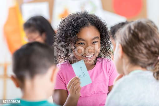 An adorable little girl sits at a table in her school classroom and holds up a flash card.