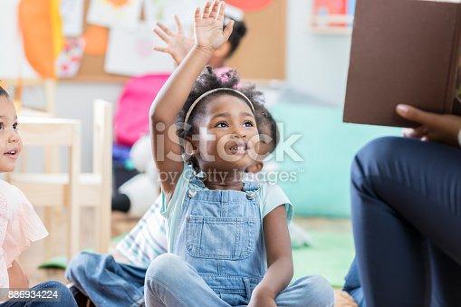 istock Little girl raises her hand during story time 886934224
